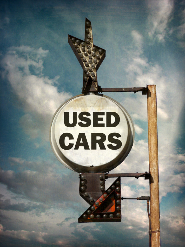 "Sign that is worn and says ""used cars""."