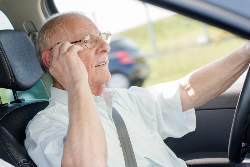 Senior citizen man that is adjusting his glasses as he drives.